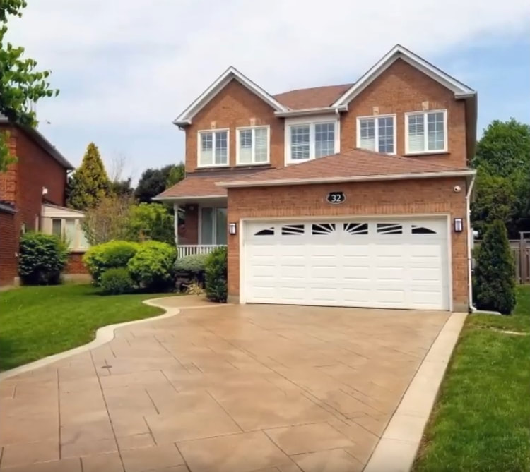 Picture of a house with a newly installed stamped concrete driveway, located in Kansas City, Kansas